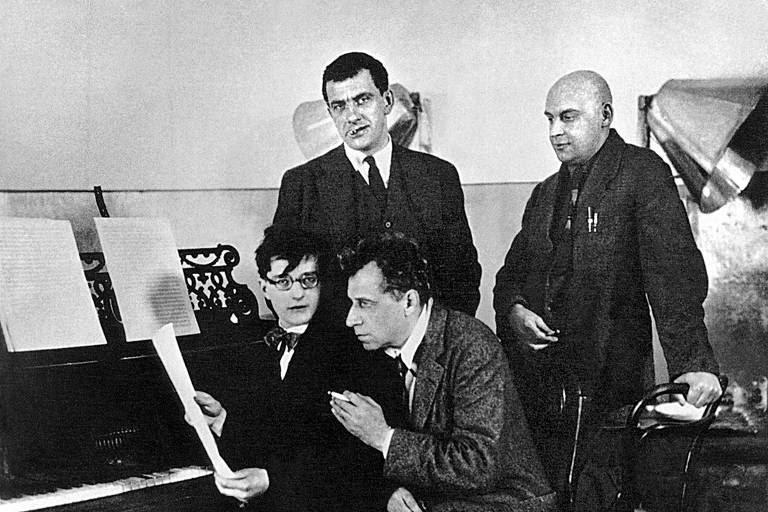 O início do período comunista teve o apoio de artistas de vanguarda, como o poeta e dramaturgo Vladímir Maiakóvski (em pé, fumando), que criou pôsteres de propaganda política para os bolcheviques