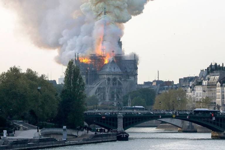 TOPSHOT - Smokes ascends as flames rise during a fire at the landmark Notre-Dame Cathedral in central Paris on April 15, 2019 afternoon, potentially involving renovation works being carried out at the site, the fire service said. (Photo by FRANCOIS GUILLOT / AFP)