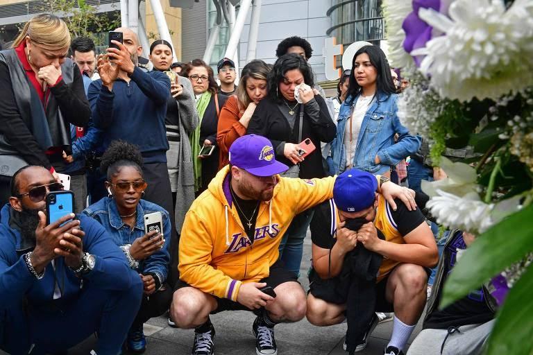 Fãs lamentam a morte de Kobe Bryant em memorial montado em frente ao estádio do Los Angeles Lakers neste domingo (26)